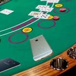An iPhone and a Samsung Android device tossed onto a blackjack table like cards