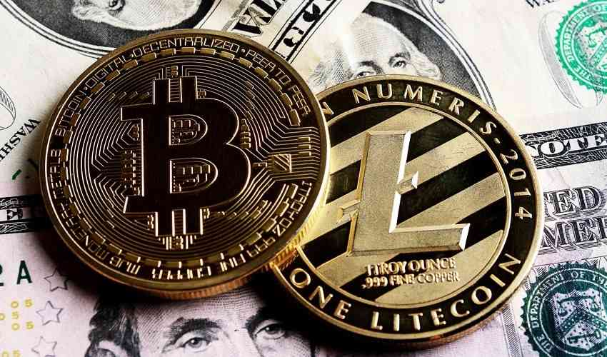 bitcoin and litecoin tokens sitting atop cash bills