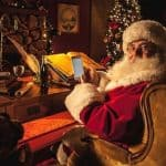 santa claus using a smartphone to gamble at his desk